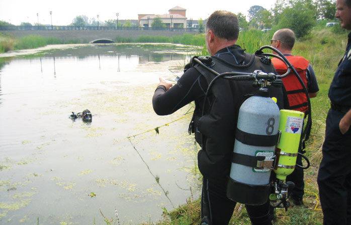 Searching for a child mannequin in a murky pond in a training exercise