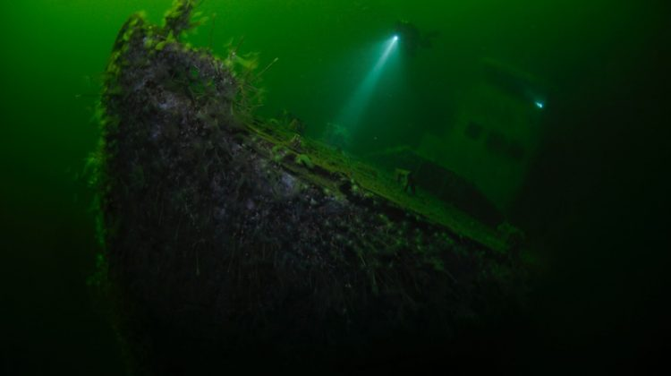 The ghostly remains of s shipwreck emerges from the dark water of the fjord (Photo by Sven Gust)