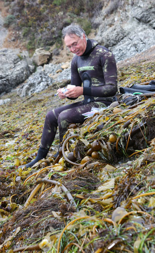 A successful abalone diver fills out his report card on the beach.