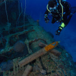 Scuba diver looks at live 5 inch shells on submarine wreck USS Apogon, Bikini Atoll