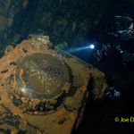Scuba diver examines radar screen in CIC on ship wreck USS Saratoga
