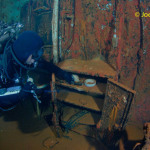 Scuba diver examines safe in dentist office on ship wreck USS Saratoga