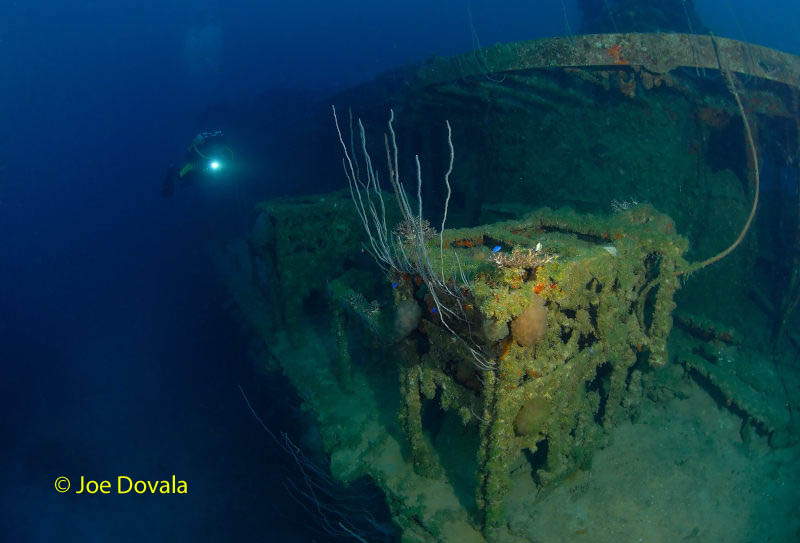 A scuba diver comes up to live depth charges at depth on ship wreck USS Lamson, Bikini Atoll.